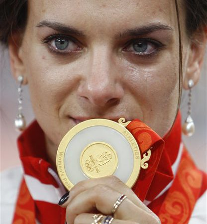 Russian pole vaulter Yelena Isinbayeva shows her gold medal during an awarding ceremony of the women's pole vault in the National Stadium at the Beijing 2008 Olympics in Beijing, Tuesday, Aug. 19, 2008. Isinbayeva won the medal with a world record. (AP Photo/Greg Baker)